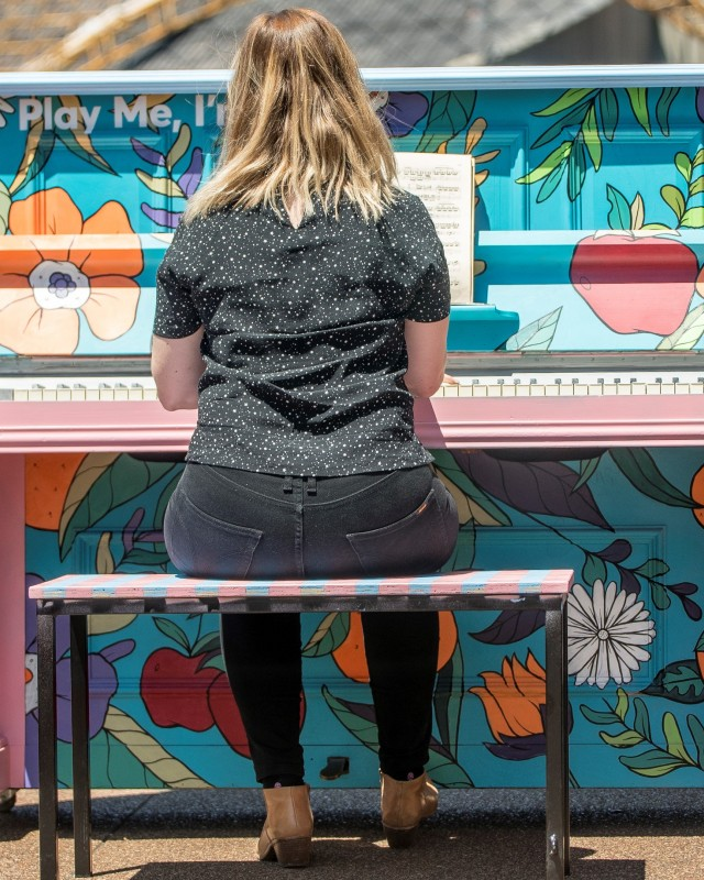 young woman playing public piano
